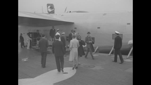 Ambassador John Cudahy is greeted by Mrs Lawrence Robert Jr at Boeing 314 Clipper / they chat at platform with water beyond and whiteuniformed...