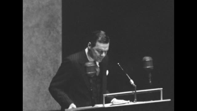 US Ambassador to UN Henry Cabot Lodge Jr standing at podium speaking quotes Pres Dwight Eisenhower as calling the UN 'the living sign of all people's...
