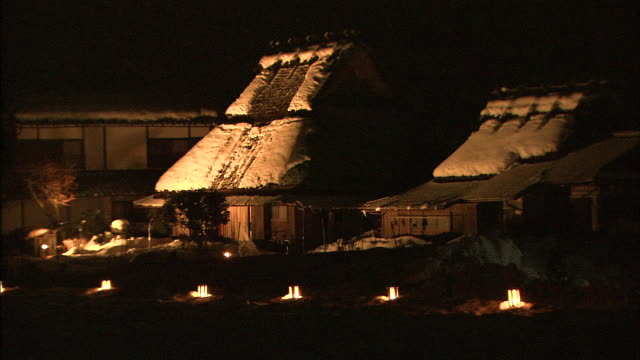 Amber lights glow on snowy rooftops in the Village of Steep Thatched Roofed Houses.