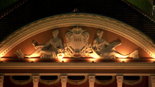 vidéos et rushes de amber lights illuminate an arched pediment on the exterior of the teatro amazonas opera house in manaus, brazil. available in hd. - fronton