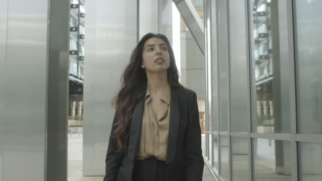 ambitious successful hispanic young adult business woman walking outside office in city wearing suit - only women stock videos & royalty-free footage