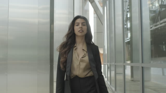 ambitious successful hispanic young adult business woman walking outside office in city wearing suit - elegance stock videos & royalty-free footage