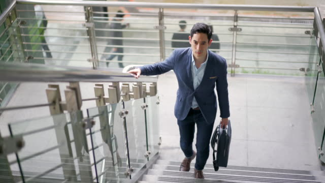 ambitious young businessman entering a corporate building - steps and staircases stock videos & royalty-free footage