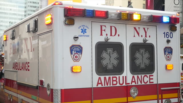 ambulance car standing on street in new york city. emergency service vehicle. public safety background - fire department of the city of new york stock-videos und b-roll-filmmaterial