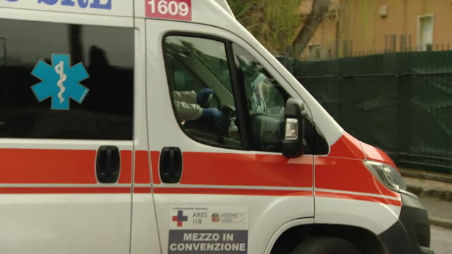 ambulance, driven by paramedic in full protective clothing leaves hospital in bologna during the coronavirus outbreak in italy - italy stock videos & royalty-free footage