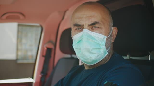 vídeos de stock e filmes b-roll de slo mo ambulance driver putting on a medical mask while looking at camera - interior de carro