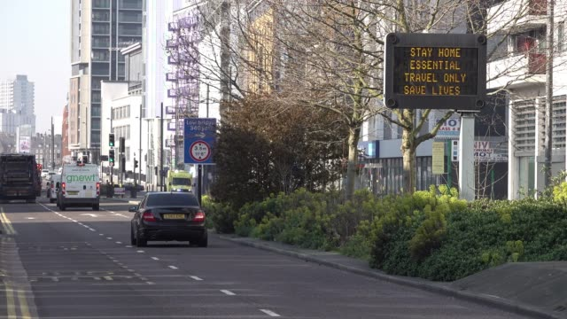 """a ambulance drives towards an led road sign in stratford warning the public to """"stay home essential travel only save lives"""" during the coronavirus... - sign stock videos & royalty-free footage"""