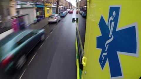 stockvideo's en b-roll-footage met ambulance driving down a road - reddingswerker