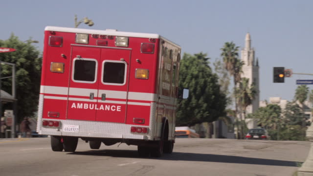 ts ambulance driving down the street / los angeles, california, united states - ambulanza video stock e b–roll