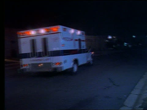 Ambulance driving on street away from camera at night
