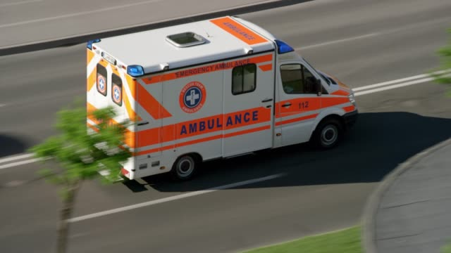 ambulance driving on the road in the city in sunshine - ambulance stock videos & royalty-free footage