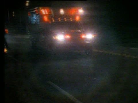 Ambulance driving toward + past camera at night
