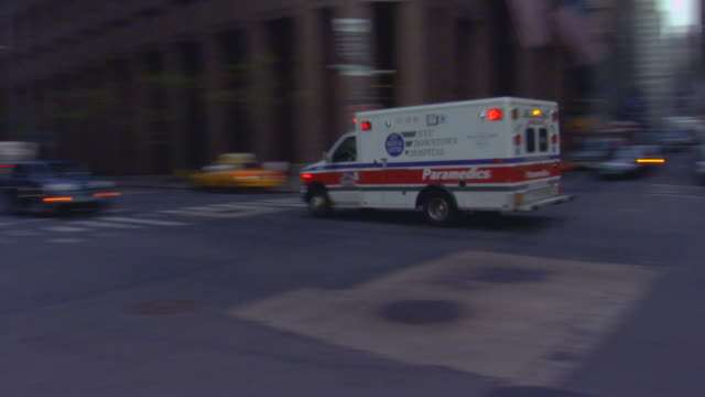 Ambulance going down a city street with lights on (handheld shot)