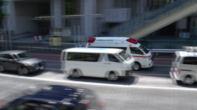 ambulance in downtown tokyo, japan - salvataggio video stock e b–roll