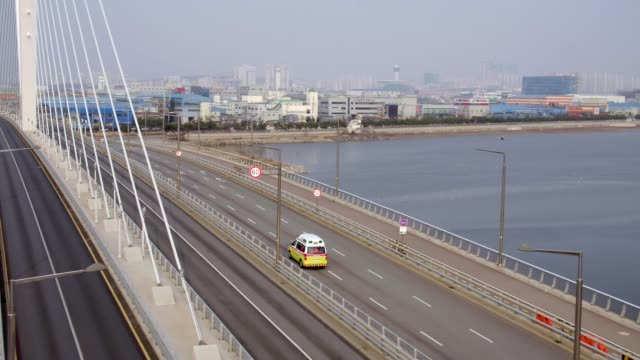 stockvideo's en b-roll-footage met ambulance moving on bio industry bridge at songdo international business district / yeonsu-gu, incheon, south korea - eerste hulp