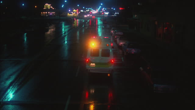 ws tu ambulance moving on wet street, small town in background - ambulance stock videos & royalty-free footage