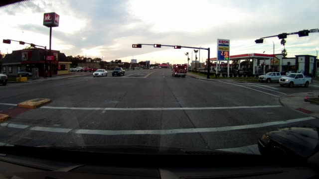 ambulance passing by and dashboard camera point of view of traffic and gas station in texas - exxon stock videos & royalty-free footage