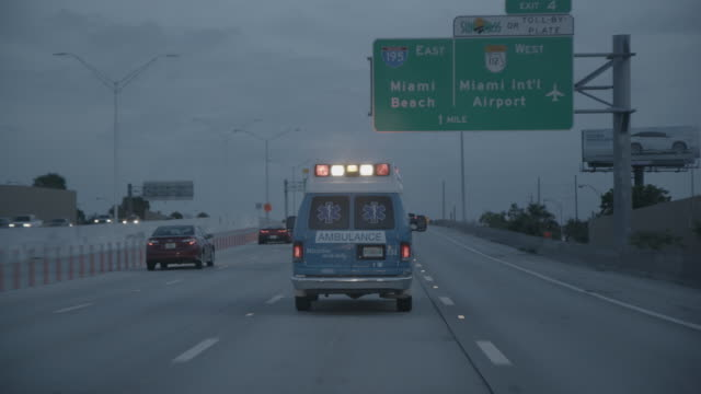 ambulance rides with sirens on florida highway - blaulicht stock-videos und b-roll-filmmaterial