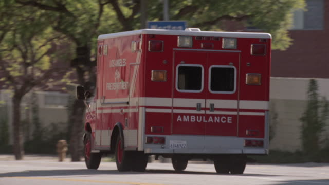 TS Ambulance speeding down a city street / Los Angeles, California, United States
