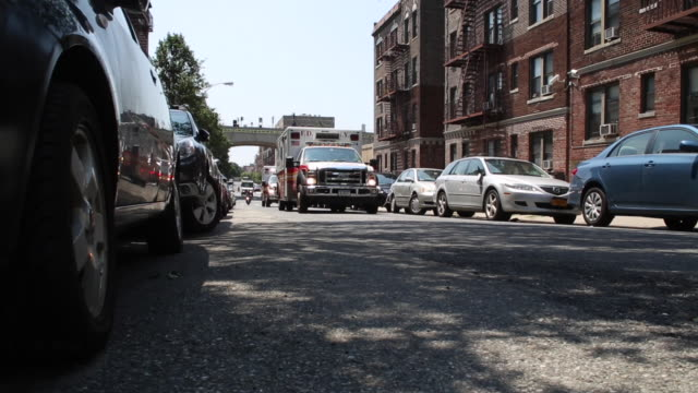 stockvideo's en b-roll-footage met ambulances and a motorcyclist drive by camera in queens new york low angle dolly shot - steekwagen