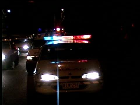 MS Ambulances parked at side of road, lights flashing, at night