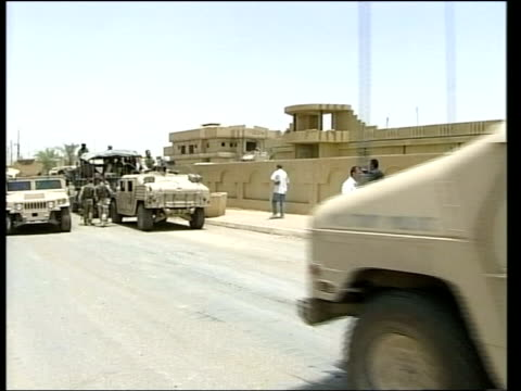 ambush/us troops storm falluja; itn day side us soldier on duty in street american armoured car towards past i/c - al fallujah bildbanksvideor och videomaterial från bakom kulisserna