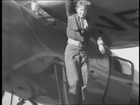 Amelia Earhart answers questions and climbs in and out of an airplane