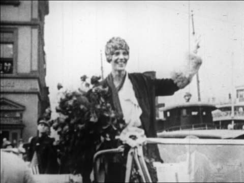 Amelia Earhart holding flowers standing in convertible waving / NYC / newsreel