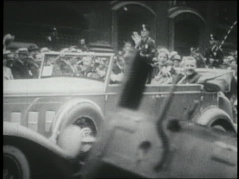 Amelia Earhart in convertible sedan waving to crowd in parade