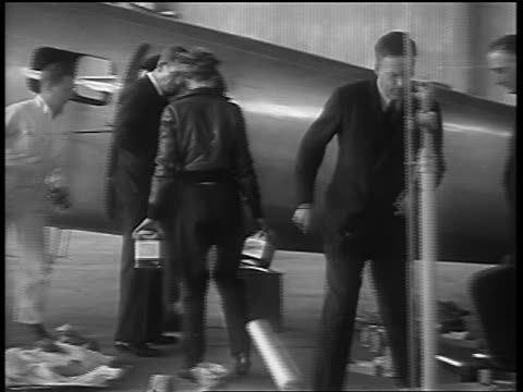 Amelia Earhart men loading airplane with supplies for final flight