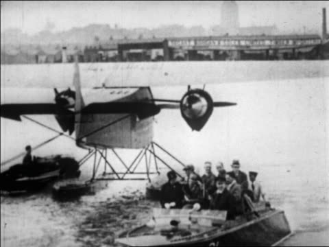 vídeos y material grabado en eventos de stock de amelia earhart + others riding motorboat away from seaplane with shoreline in background - 1928