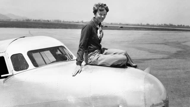 Amelia Earhart poses on the nose of a Lockheed Electra monoplane.