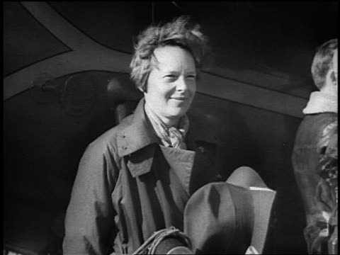 Amelia Earhart smiling standing near aircraft after transPacific flight