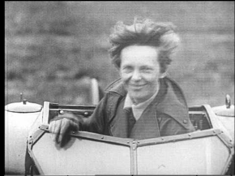 Amelia Earhart waving from cockpit of airplane before transAtlantic flight
