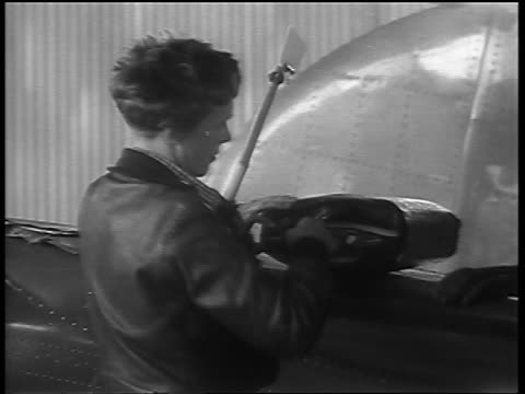Amelia Earhart zipping full bag near aircraft outdoors before final flight / Oakland CA