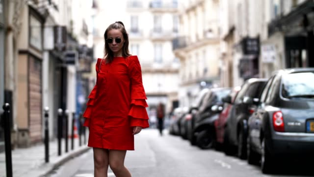 vidéos et rushes de amelie lloyd, fashion blogger, wears a journee red ruffled dress, a valentino bag, sunglasses, and white sneakers, on may 13, 2017 in paris, france. - blog