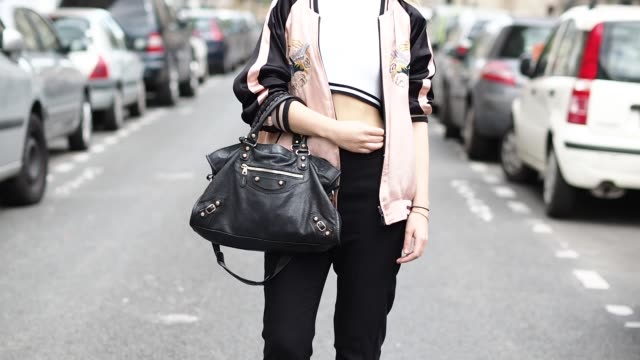 amelie lloyd wears a zara pink bombers jacket another stories black pants a forever 21 top minelli shoes a balenciaga bag and ray ban sunglasses... - amelie lloyd stock videos and b-roll footage