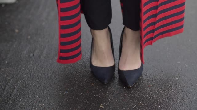 amelie lloyd wears zara heels and other stories pants a tommy hilfiger top an isabel marant red striped coat and a furla bag outside the valentino... - tommy hilfiger designer label stock videos and b-roll footage