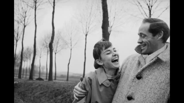 american actor mel ferrer buttons up his coat around his wife, actress audrey hepburn , on a country road outside paris, 1956. - audrey hepburn stock videos & royalty-free footage
