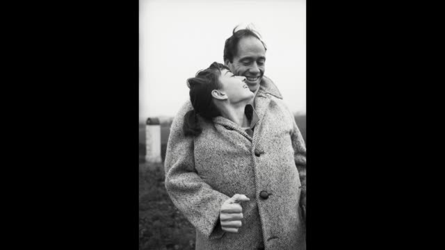 GIF American actor Mel Ferrer buttons up his coat around his wife actress Audrey Hepburn on a country road outside Paris 1956