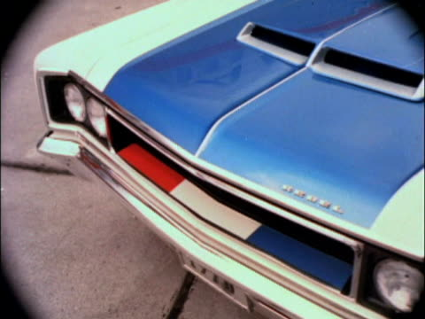 MS American Airline passenger plane wing moves out of view to reveal a 1970 AMC Rebel Machine muscle car sitting on the tarmac / MS HA vignette shot...