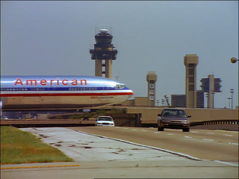 American Airlines airplane taxiing with traffic on highway in foreground at Dallas-Fort Worth Airport / Texas