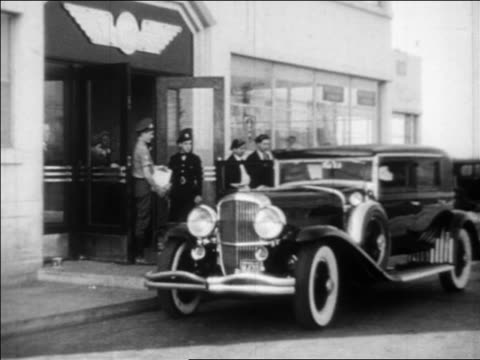 B/W 1933 American Airlines limousine stopping at curb at airport + movie star gets out / industrial