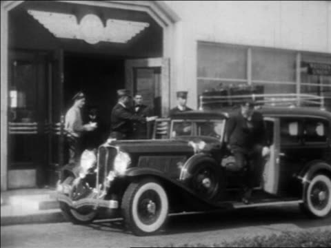 B/W 1933 American Airlines limousine stopping at curb at airport + people get out / industrial