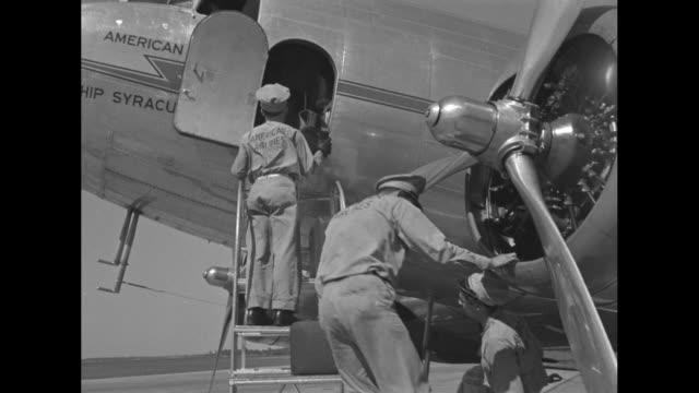 American Airlines workers pass luggage into a DC3 / an airplane starts to taxi away on tarmac / three men in suits climb the gangway to the interior...