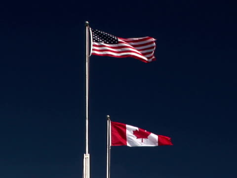 MS American and Canadian flags flapping against clear sky