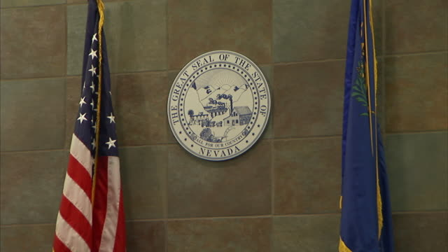 american and city of las vegas flags pillar a state of nevada crest in a courtroom. - nevada stock-videos und b-roll-filmmaterial