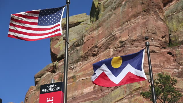 MS American and Colorado flag with red rocks in background / Denver, Colorado, United States