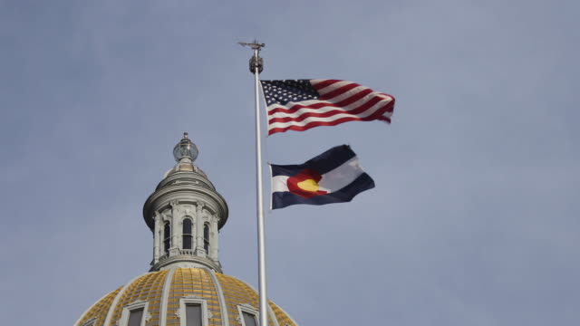 vidéos et rushes de american and colorado state flags flying in denver - colorado