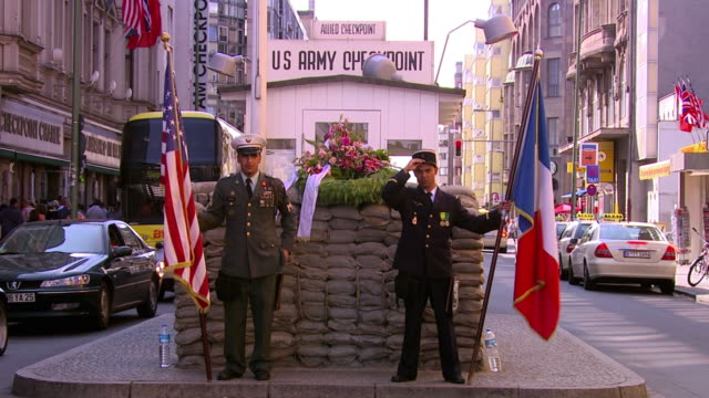 vídeos de stock, filmes e b-roll de ws american and french soldier with flags at checkpoint charlie, berlin wall crossing point between east germany and west germany during cold war / berlin, germany - east berlin